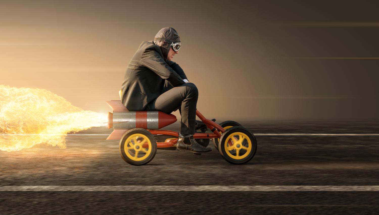 uomo su macchina a pedali spinta da un razzo